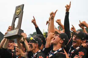 Edwardsville celebrates with the Class 4A state championship trophy after defeating St. Charles North 3-2 in eight innings on Saturday in Joliet.