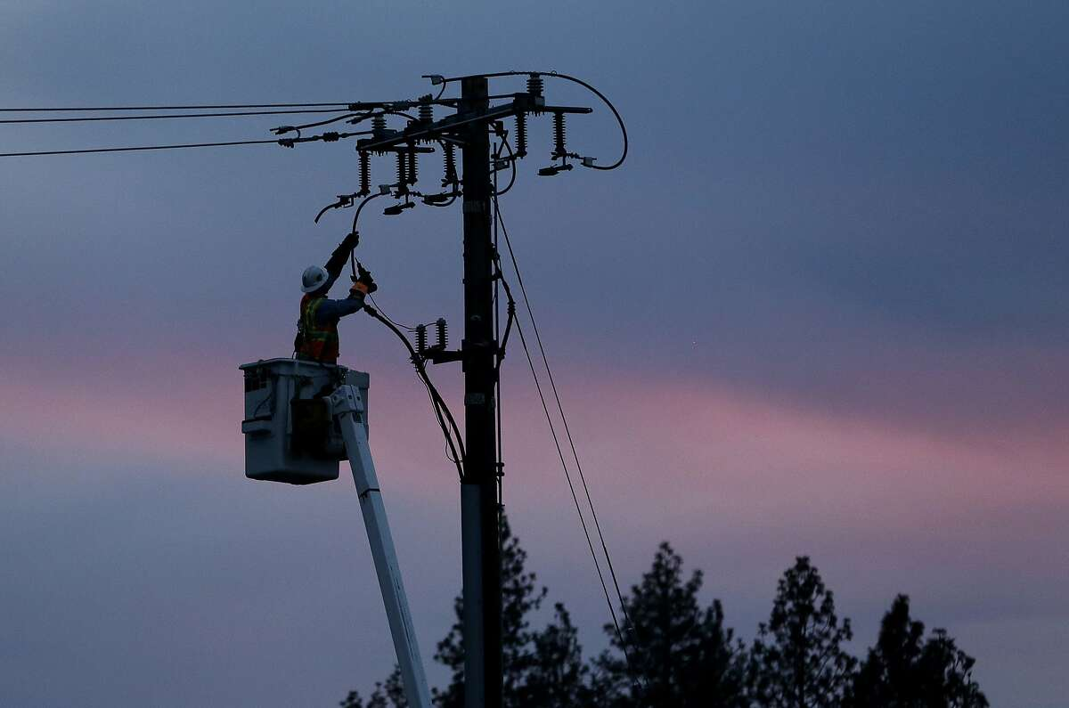 FILE - In this Nov. 26, 2018, file photo, a Pacific Gas & Electric lineman works to repair a power line in fire-ravaged Paradise, Calif. Pacific Gas & Electric said it will shut off power Saturday, June 8, to about 1,600 customers in Northern California and may do the same for thousands more to reduce the risk of wildfires. The utility announced Friday night that as of Saturday morning it will turn off electricity to customers in Napa, Solano and Yolo counties west of Sacramento. (AP Photo/Rich Pedroncelli, File)