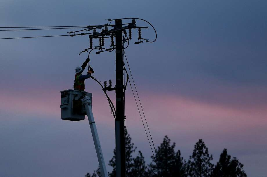 In this Nov. 26, 2018, file photo, a PG&E worker repairs a power line in fire-ravaged Paradise (Butte County) in November. The utility is cutting off power to areas of Northern California at risk as a precaution. Photo: Rich Pedroncelli / Associated Press