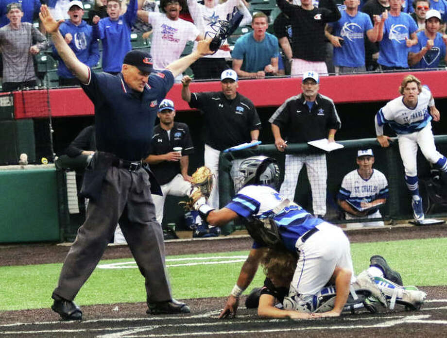 Plate umpire Craig Davelis (left) makes the safe call while St. Charles North catcher Marco Torres shows him the ball and Edwardsville's Aaron Young keeps his hands on the plate after scoring from second base on a bunt for the winning run in the eighth inning of the Class 4A baseball state tournament championship game Saturday night in Joliet. Photo: Greg Shashack / The Telegraph