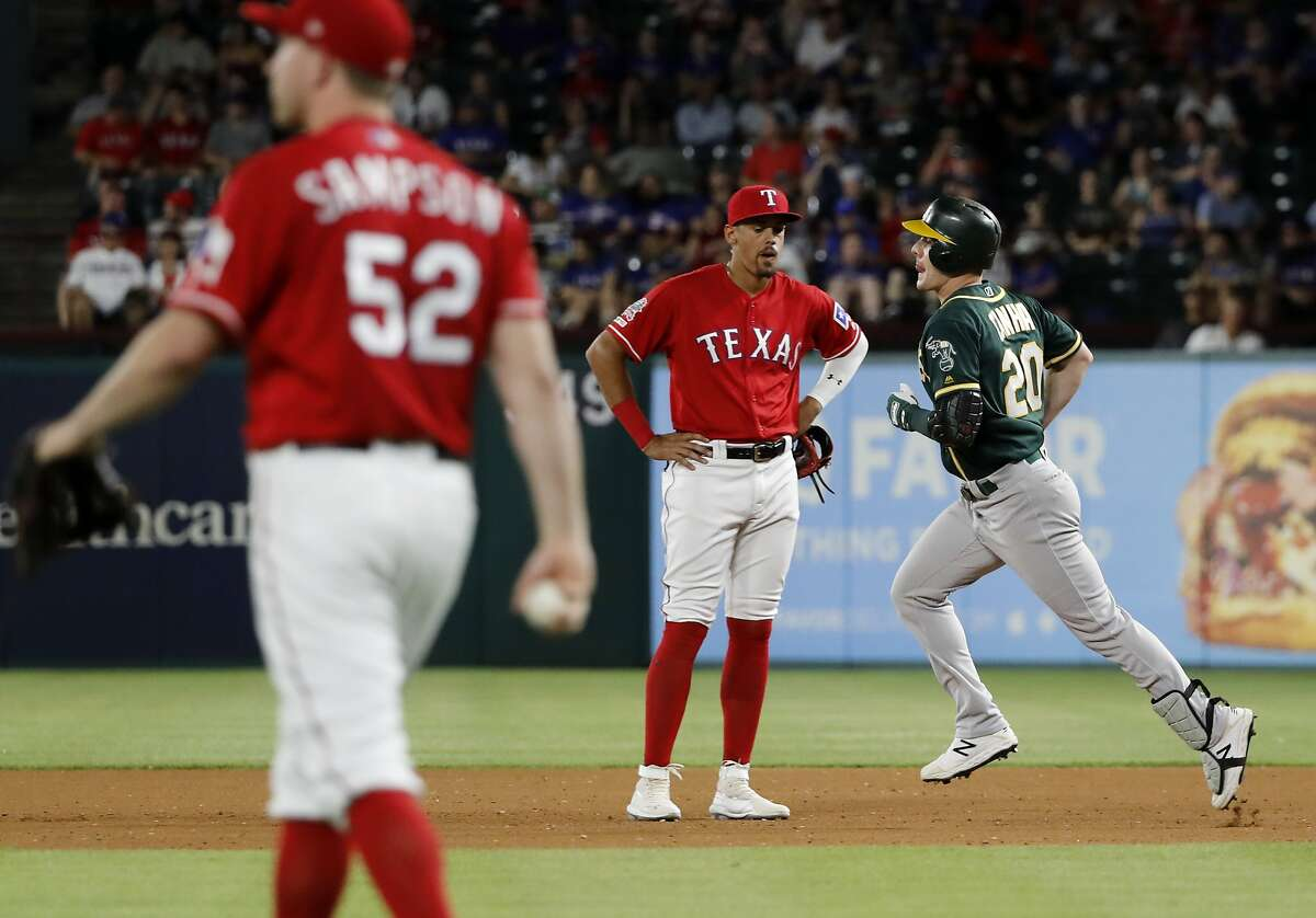 Texas Rangers' Adrian Sampson (52) walks back to the mound as first baseman Ronald Guzman watches Oakland Athletics' Mark Canha, right, round the bases on a solo home run in the fourth inning of the second baseball game of a doubleheader in Arlington, Texas, Saturday, June 8, 2019. (AP Photo/Tony Gutierrez)