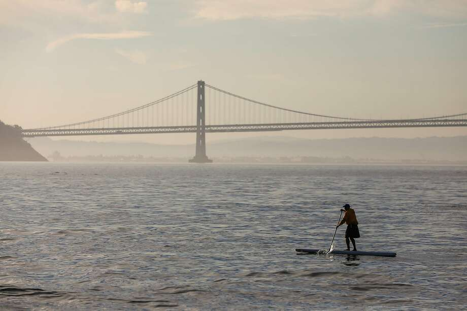 A man paddleboards at sunrise passing by the Bay Bridge during the Escape from Alcatraz triathalon in San Francisco, California, on Sunday, June 9, 2019. Photo: Gabrielle Lurie / The Chronicle
