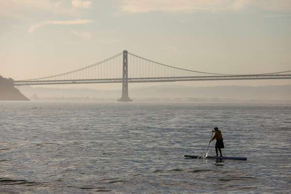 A man paddleboards at sunrise passing by the Bay Bridge during the Escape from Alcatraz triathalon in San Francisco, California, on Sunday, June 9, 2019.