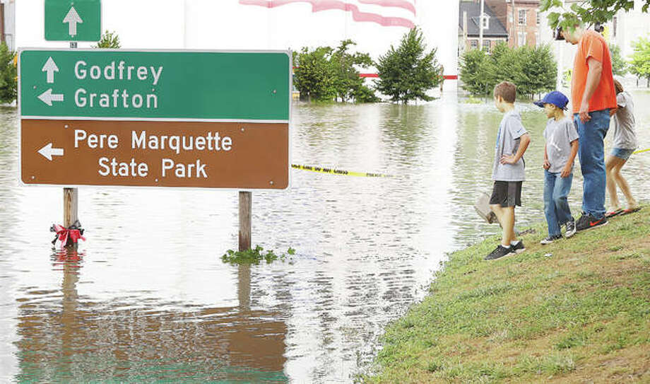 A man with three children visit the edge of the historic flooding in downtown Alton. Seeing the flood that topped the record of 1844 to become the second worst in recorded history may be a once in a lifetime event for many area residents.