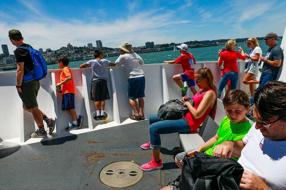 People sit out in the sun as they ride the boat from Alcatraz to San Francisco in San Francisco, California, on Sunday, June 9, 2019. Photo: Gabrielle Lurie, The Chronicle