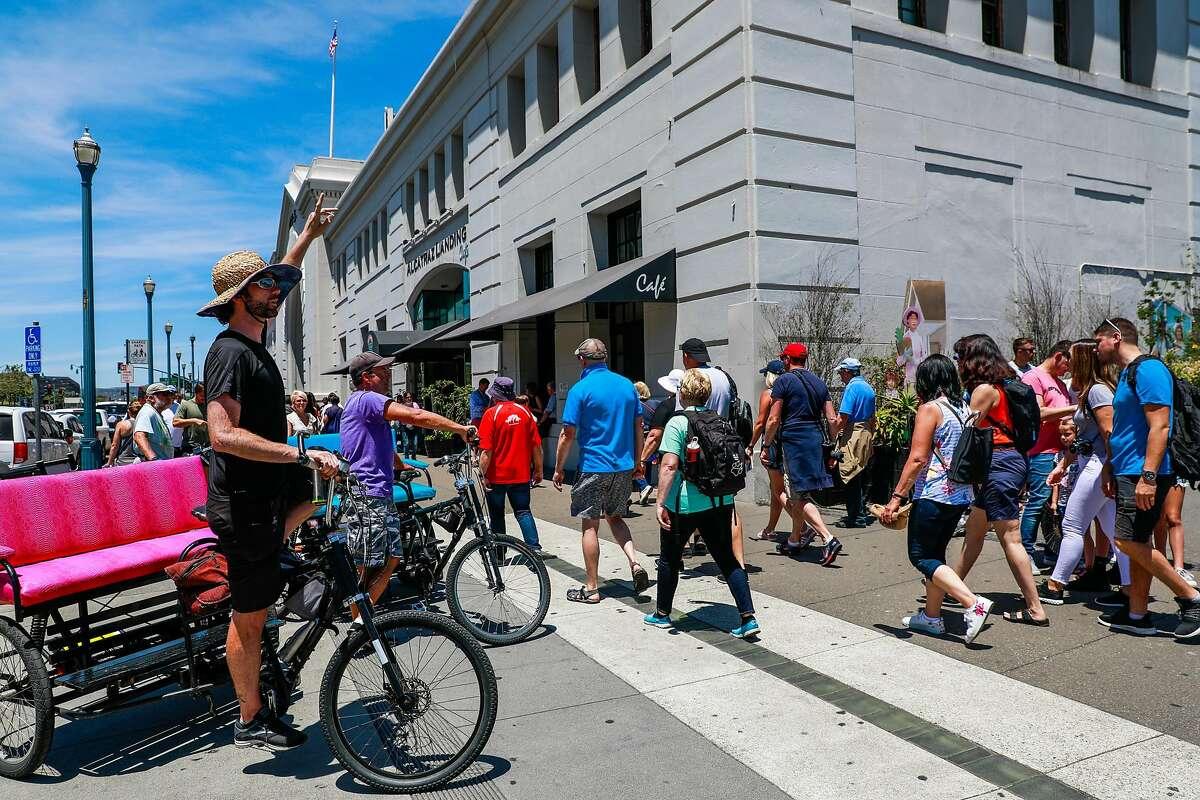 People walk along the Embarcadero in the sun in San Francisco, California, on Sunday, June 9, 2019.