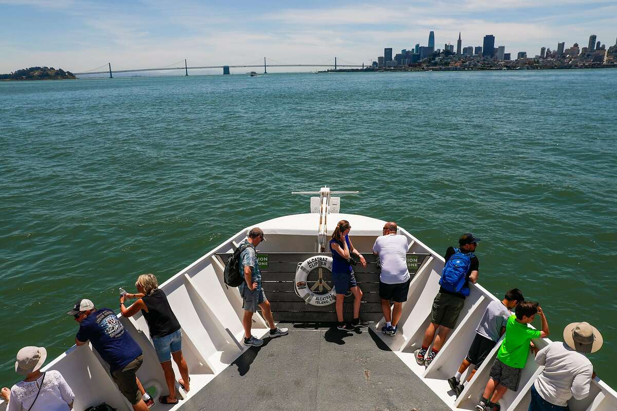 People stand outside in the sun as they ride the boat from Alcatraz to San Francisco in San Francisco, California, on Sunday, June 9, 2019.
