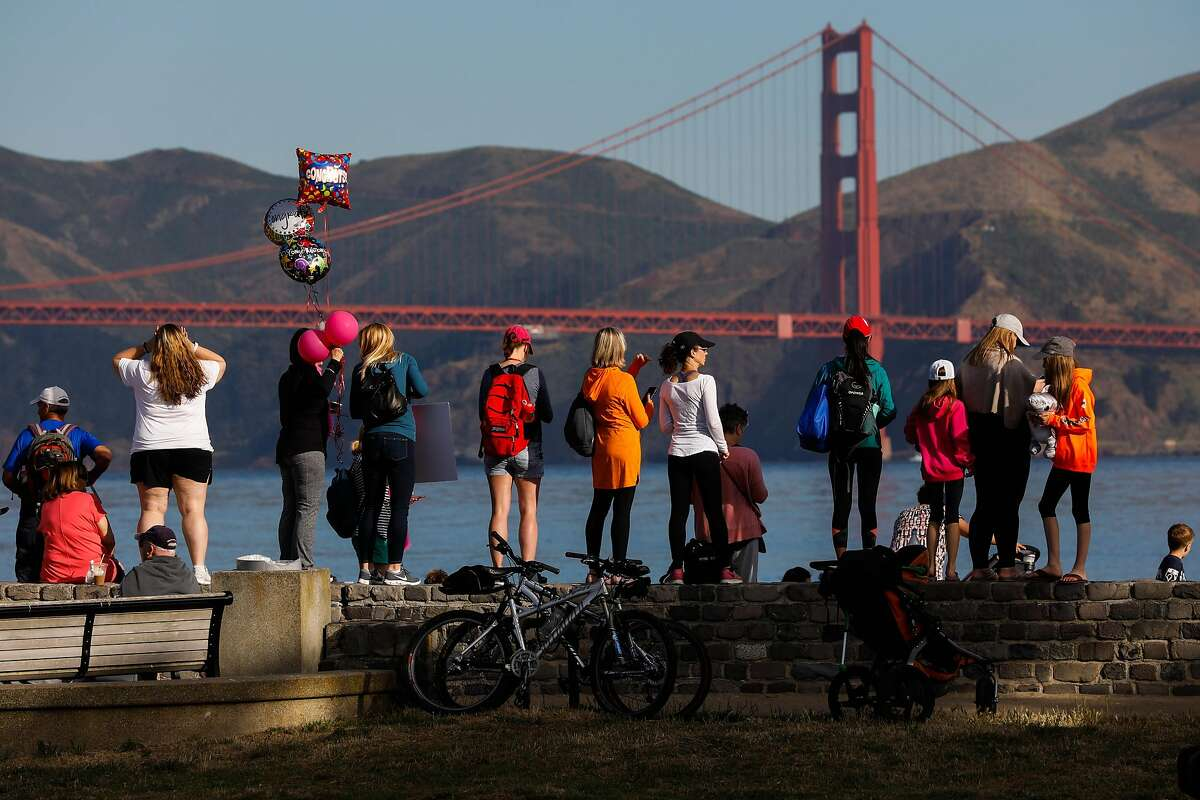 Spectators wait for the first swimmers to appear during the 39th annual Escape from Alcatraz Triathalon in San Francisco, California, on Sunday, June 9, 2019. Over 2,000 athletes swam the 1.5 miles to shore followed by an 18-mile bike ride and an 8-mile run through San Francisco. The race is considered one of the oldest and most difficult triathlons with many elite participants.