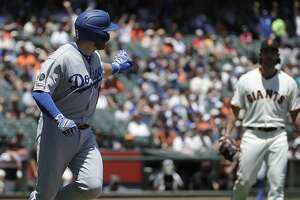 Los Angeles Dodgers' Max Muncy, left, gestures while running up the first base line after hitting a solo home run off of San Francisco Giants pitcher Madison Bumgarner, right, during the first inning of a baseball game in San Francisco, Sunday, June 9, 2019. (AP Photo/Jeff Chiu)