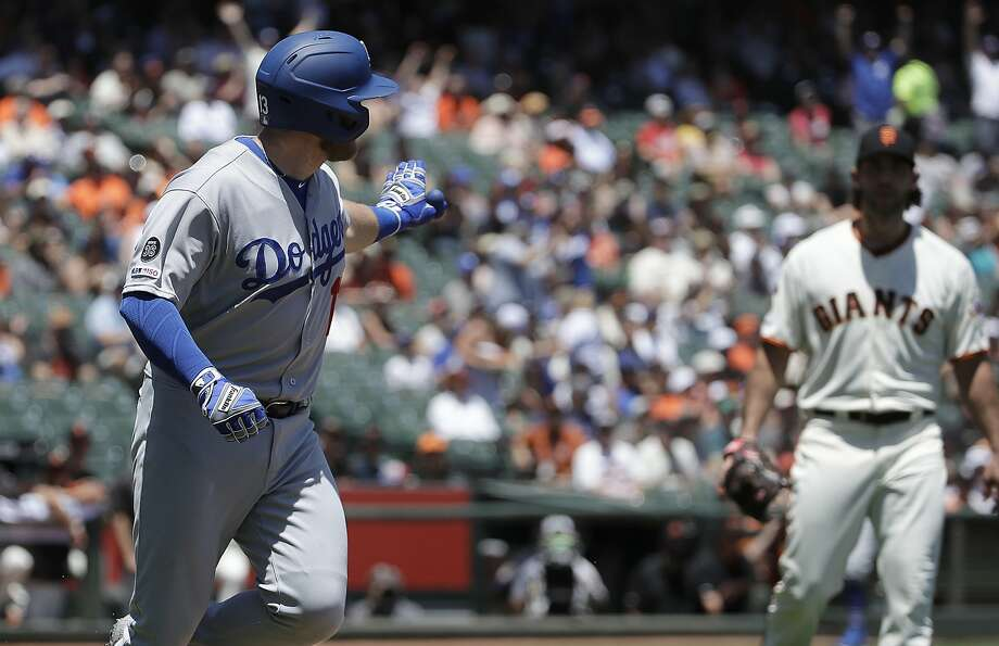 Los Angeles Dodgers' Max Muncy, left, gestures while running up the first base line after hitting a solo home run off of San Francisco Giants pitcher Madison Bumgarner, right, during the first inning of a baseball game in San Francisco, Sunday, June 9, 2019. (AP Photo/Jeff Chiu) Photo: Jeff Chiu, Associated Press