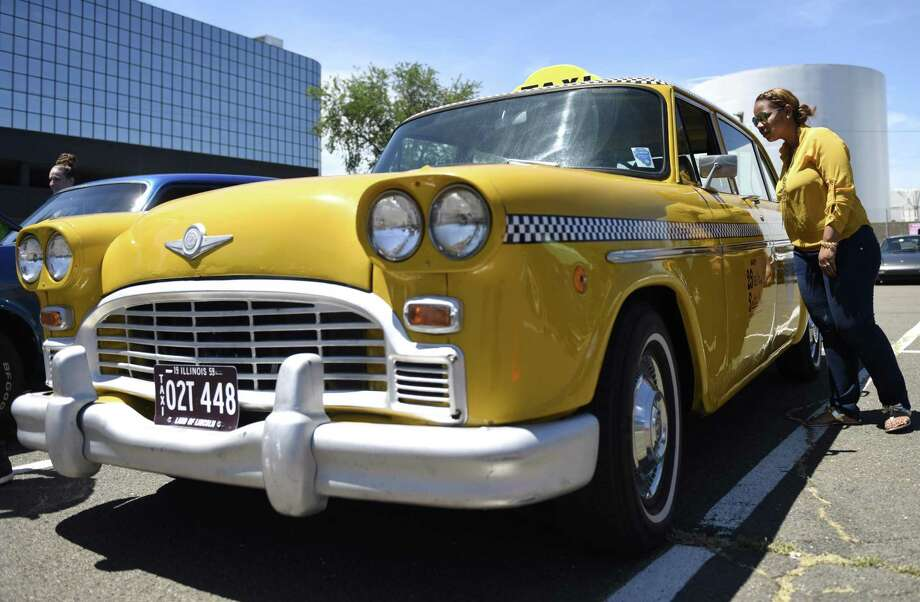 Stamford's Orlendy Felciano looks at a 1959 CMC Checker Chicago taxi cab at the Fifth Annual Harbor Point Car Show in Stamford, Conn. Sunday, June 9, 2019. The show, benefiting the Boys & Girls Club of Stamford, featured hot rods, vintage cars, import tuners, American muscle cars and more. Photo: Tyler Sizemore / Hearst Connecticut Media / Greenwich Time