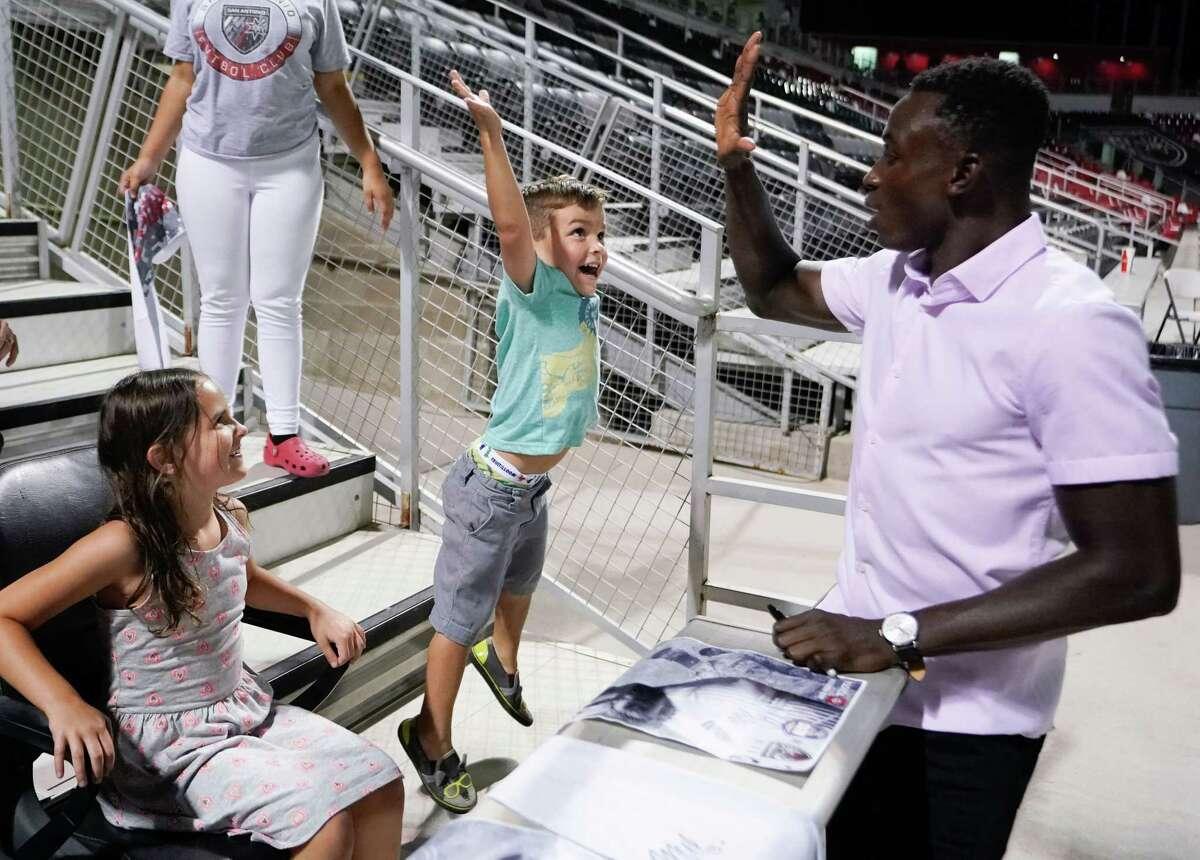 San Antonio FC defender Joshua Yaro high-fives a small fan during military appreciation night.