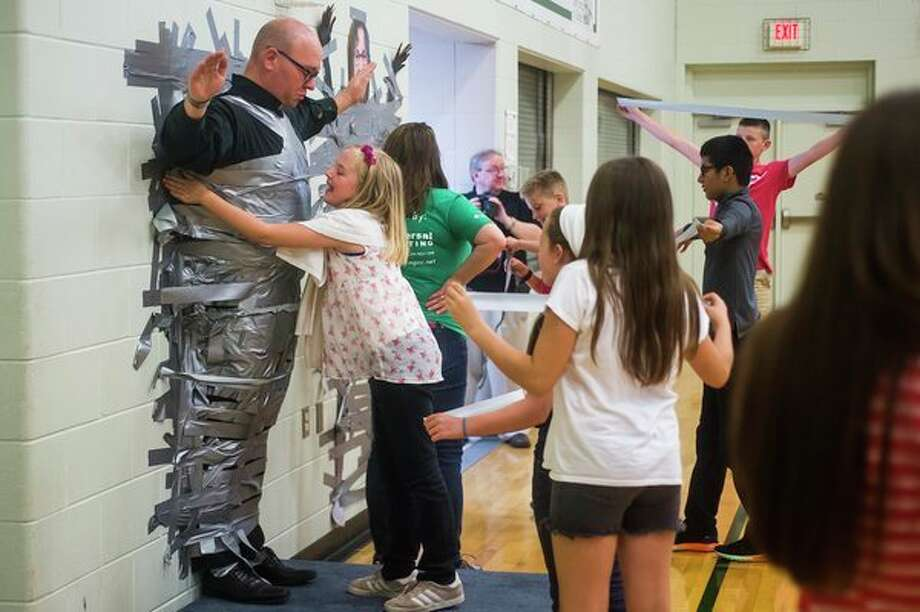 A sticky situation 				Students at St. Brigid Catholic School take turns adding pieces of duct tape as Father Andy Booms is taped to the wall during a celebration of the school's Guardian Angel Walkathon Fundraiser on Friday at the school. (Katy Kildee/kkildee@mdn.net)