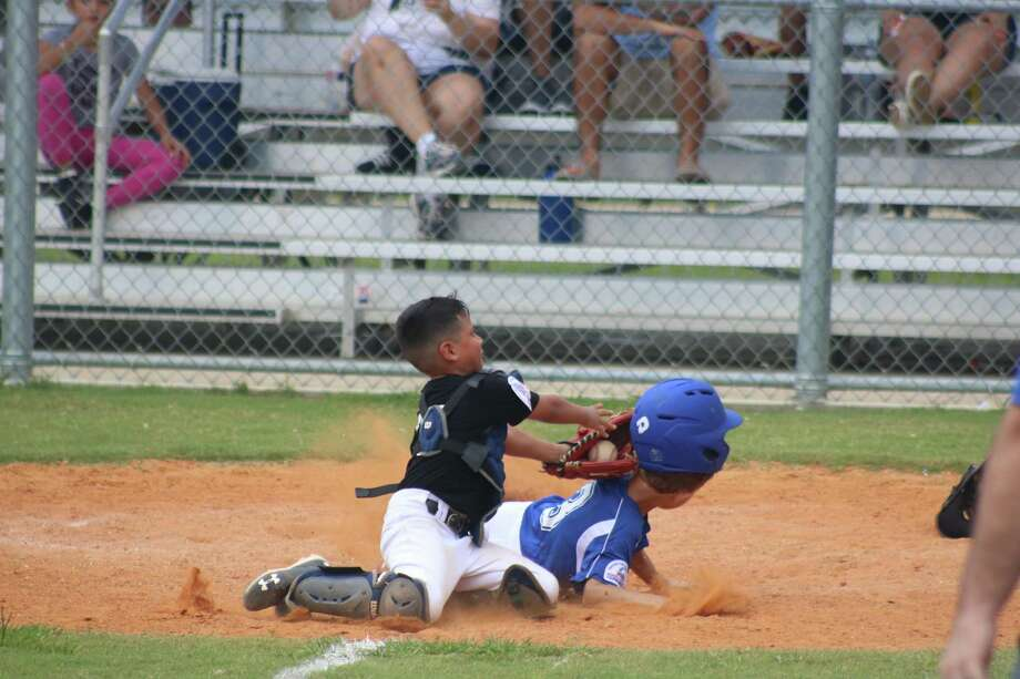 La Porte catcher Christian Quintero applies the dramatic game-ending tag on Friendswood's John Carver, who was trying to score the tying run in Sunday afternoon's championship game of the Pinto Directors Tournament. Photo: Robert Avery