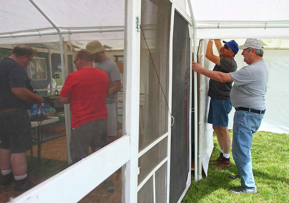 Members of St. Mary's Catholic Church in New Berlin set up the church's pork chop stand Saturday at the Sangamon County fairgrounds. The pork chop stand has been a staple at the fair for more than three decades. Photo: Rosalind Essig | Journal-Courier