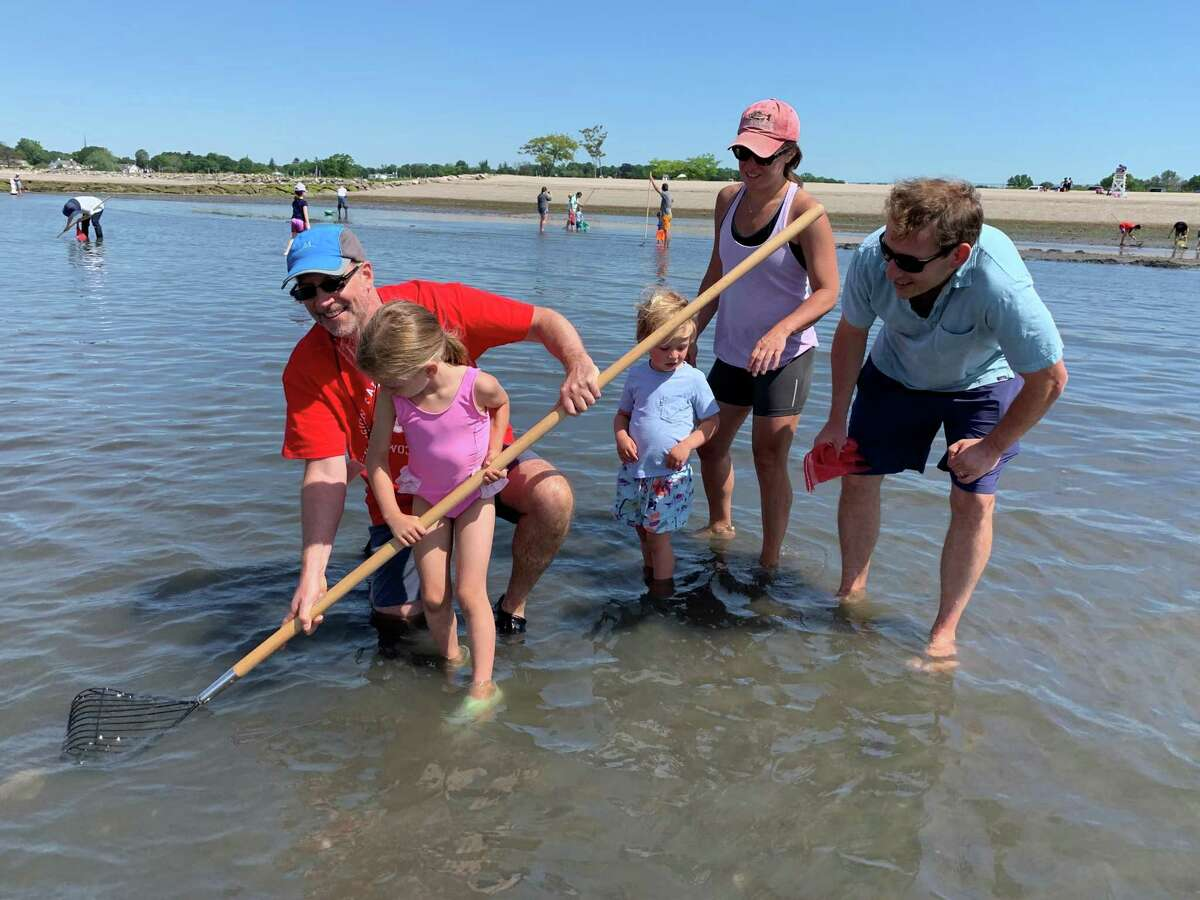Katie Cook, with her kids Anna and Will, get some tips from a member of the Fairfield Shellfish Commission during the Clam Clinic last Saturday.