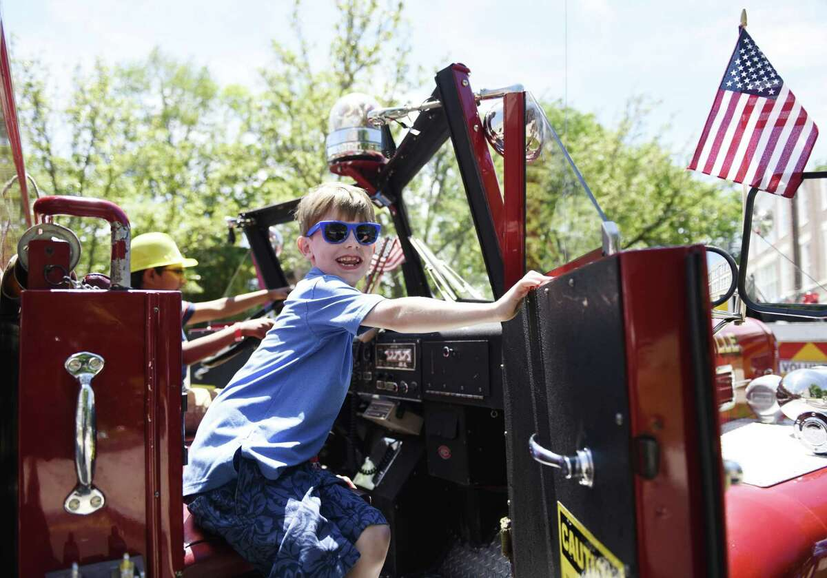 Glenville's David Bacon, 7, climbs in an antique firetruck at the 17th annual Touch a Truck event at Town Hall in Greenwich, Conn. Sunday, June 9, 2019. The kids event benefits the Junior League of Greenwich and features powerful trucks from Greenwich's Department of Public Works as well as firetrucks, police cars and motorcycles, ambulances, and heavy duty construction vehicles. Additionally, there were a wide variety of kids activities, musical performances, and food trucks.
