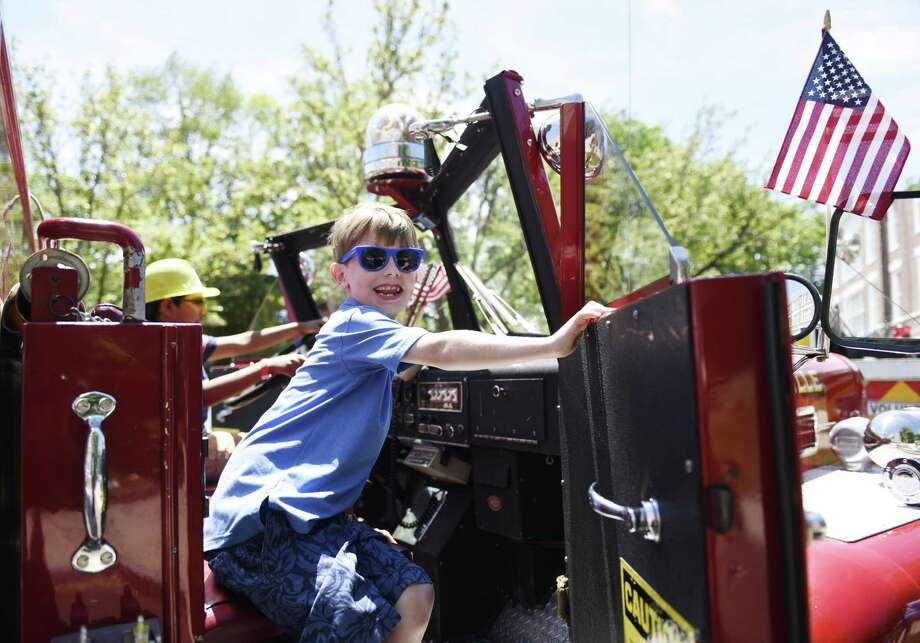 Glenville's David Bacon, 7, climbs in an antique firetruck at the 17th annual Touch a Truck event at Town Hall in Greenwich, Conn. Sunday, June 9, 2019. The kids event benefits the Junior League of Greenwich and features powerful trucks from Greenwich's Department of Public Works as well as firetrucks, police cars and motorcycles, ambulances, and heavy duty construction vehicles. Additionally, there were a wide variety of kids activities, musical performances, and food trucks. Photo: Tyler Sizemore / Hearst Connecticut Media / Greenwich Time