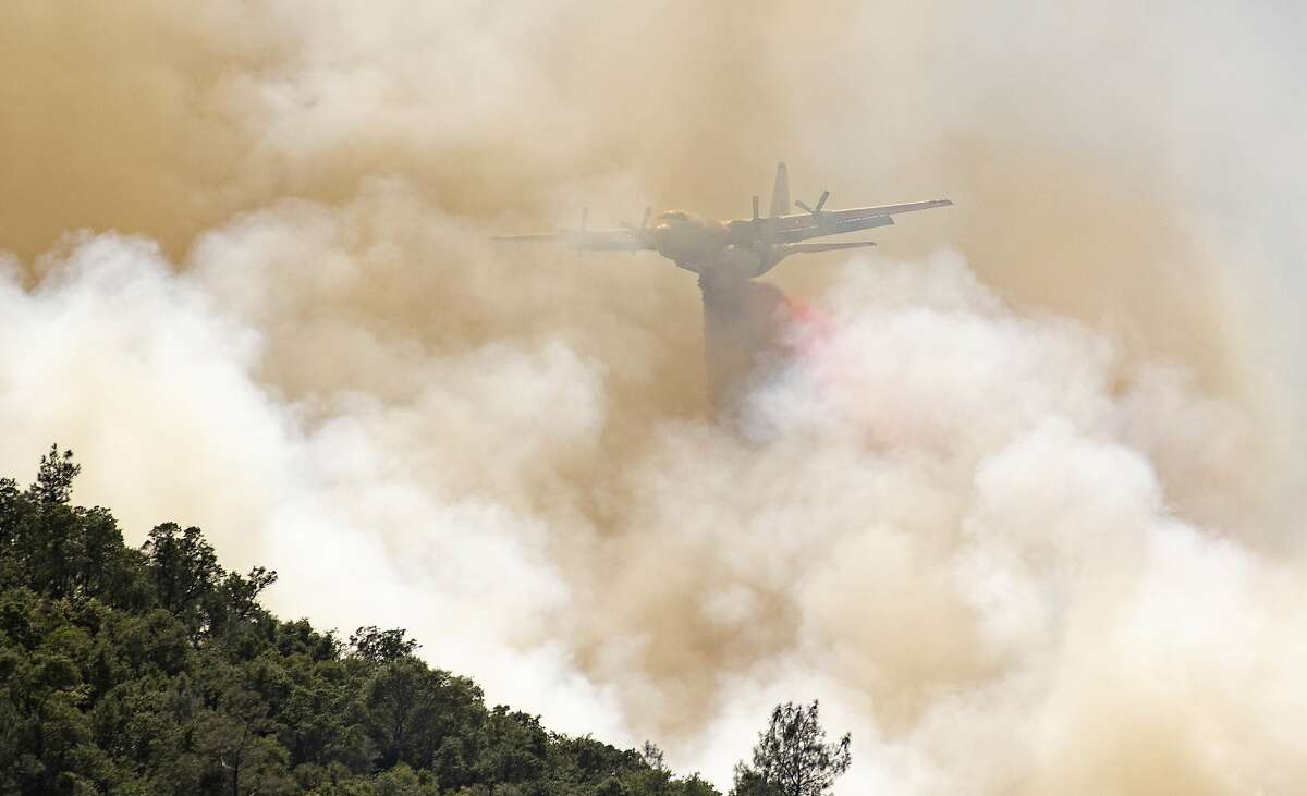 A firefighting aircraft drops fire retardant on a hillside in an attempt to box in flames from a wildfire locally called the Sand Fire in Rumsey, Calif., Sunday, June 9, 2019. (AP Photo/Josh Edelson)