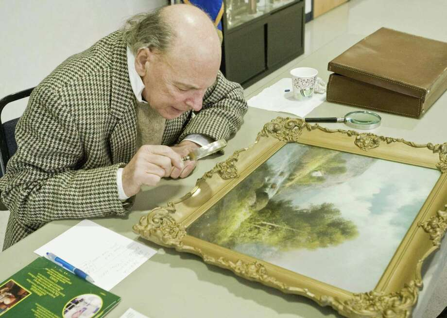 Appraiser Jay St. Mark of Newtown examines a painting at Bethel Historical Society's Antiques and Collectibles Appraisal Day at the Stony Hill Firehouse in Bethel. Saturday, March 25, 2017. Bethel Historical Society is collecting items, including artwork, for its tag sale from 9 a.m. to 3 p.m. Saturday, June 15. Photo: Scott Mullin / For Hearst Connecticut Media / The News-Times Freelance