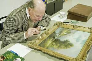 Appraiser Jay St. Mark of Newtown examines a painting at Bethel Historical Society's Antiques and Collectibles Appraisal Day at the Stony Hill Firehouse in Bethel. Saturday, March 25, 2017. Bethel Historical Society is collecting items, including artwork, for its tag sale from 9 a.m. to 3 p.m. Saturday, June 15.