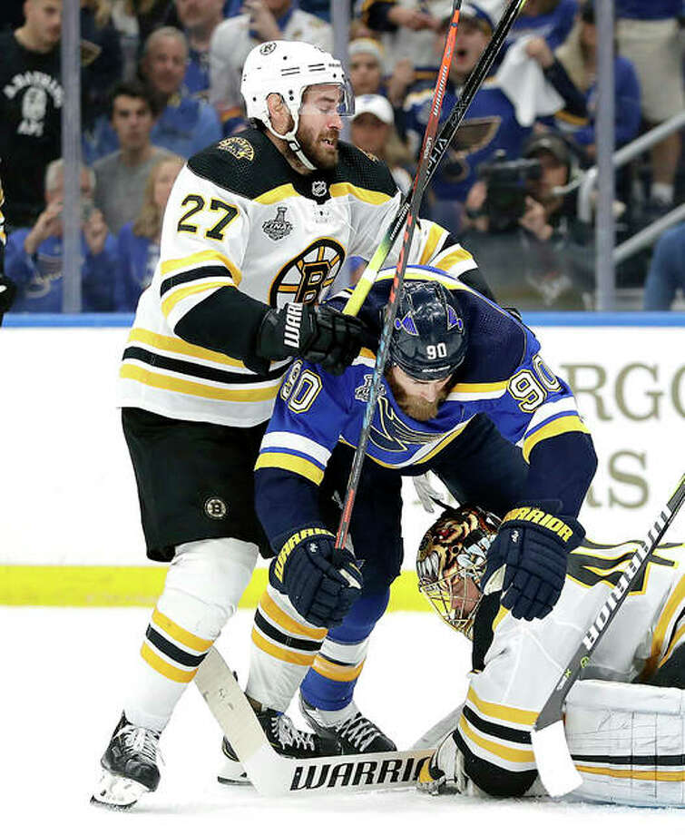 Blues center Ryan O'Reilly (90) falls between Boston Bruins defenseman John Moore (27) and goaltender Tuukka Rask (40) in Game 6 of the Stanley Cup Final Sunday night in St. Louis. Photo: Jeff Roberson | AP Photo