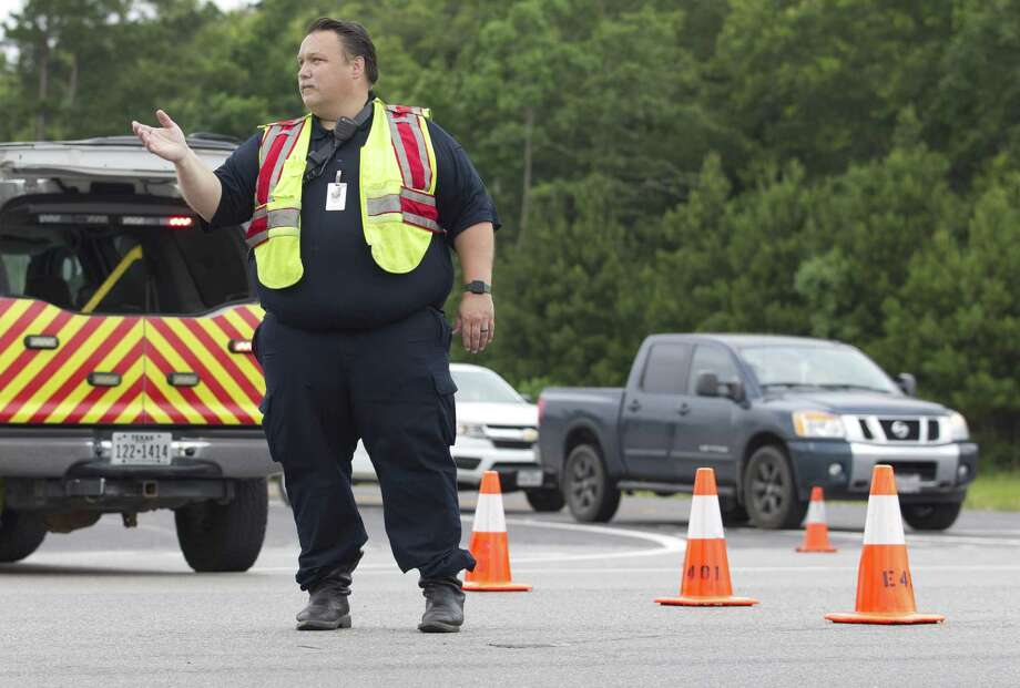 Cleveland Fire Chief Sean Anderson helps reroute traffic after Houston Street east of Grand Oaks Parkway is shutdown following an officer-involved shooting at Big Thicket Veterinary Clinic, Wednesday, May 29, 2019, in Cleveland. The suspect who fled from the scene shot a deputy with the Liberty Sheriff's Office who was in pursuit. Law enforcement are still searching for the suspect, and the deputy was transported by helicopter for treatment. Photo: Jason Fochtman, Houston Chronicle / Staff Photographer / © 2019 Houston Chronicle