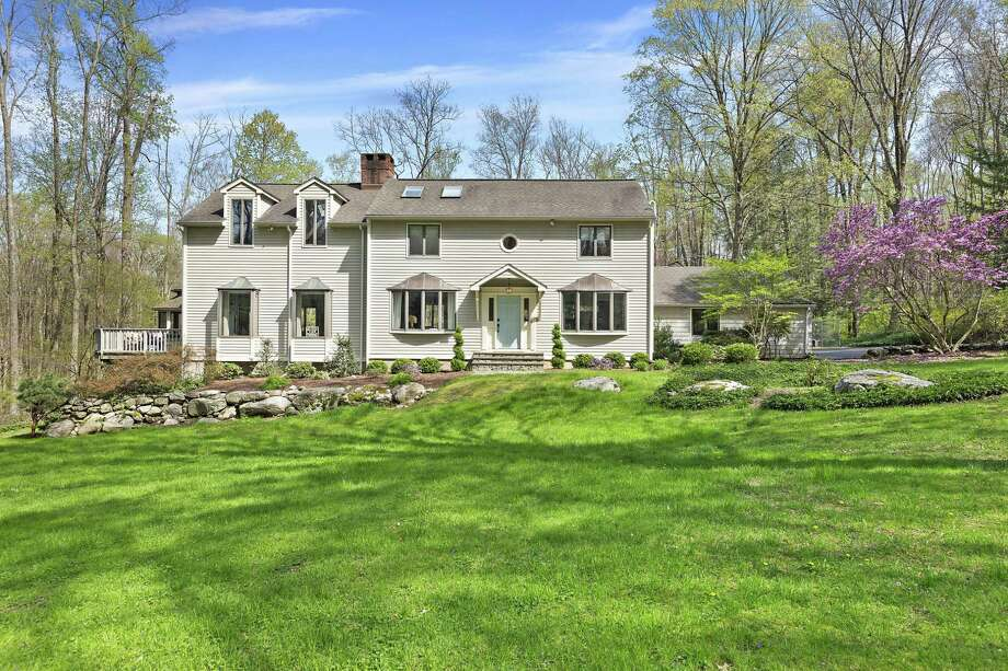 The white clapboard colonial house at 41 Godfrey Road West in Weston is within walking distance of Devil's Den Nature Preserve.