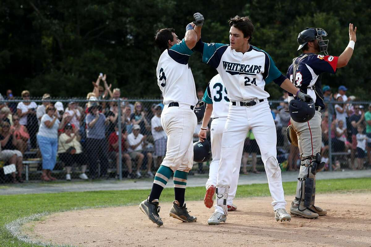 BREWSTER, MA - AUGUST 11: Hunter Bishop, right, celebrates with Michael Gasper of the Brewster Whitecaps during game one of the Cape Cod League Championship Series against the Bourne Braves at Stony Brook Field on August 11, 2017 in Brewster, Massachusett