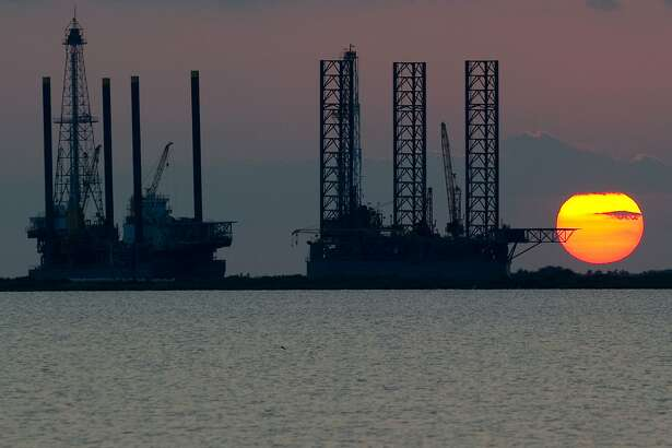 """(FILES) In this file photo taken on June 13, 2010, the sun sets behind two offshore oil platform under construction in Port Fourchon, Louisiana. - The US oil price dove into a """"bear market"""" on May 5, 2019, following a surprising jump in US petroleum inventories and as myriad trade conflicts dim the outlook for global growth. The decline in the oil market came as Wall Street stocks rallied for a second straight session on dovish commentary from the Federal Reserve and as European bourses climbed modestly ahead of a European Central Bank meeting. (Photo by Saul LOEB / AFP)SAUL LOEB/AFP/Getty Images"""