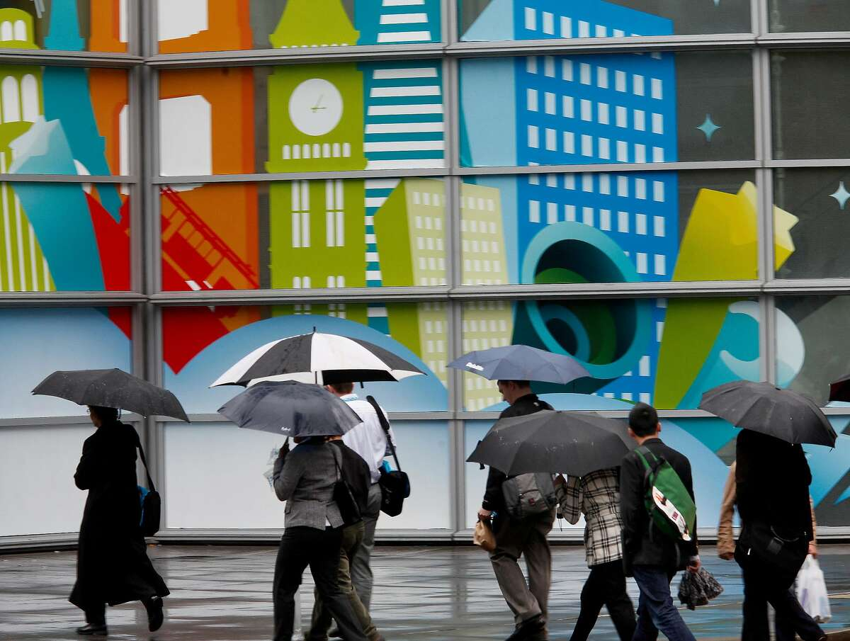 On Fourth Street near downtown San Francisco, people hurried past a mural for a salesforce.com convention in town. Umbrellas were a common sight in most of the Bay Area Wednesday, December 8, 2010 , as a stubborn rain fell most of the day.