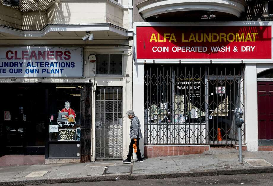 A woman walks past empty storefronts along Grant Avenue in North Beach, among the neighborhoods with the highest retail vacancy rates in the city. Photo: Jessica Christian / The Chronicle