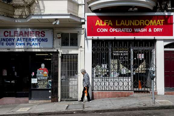 A woman walks past empty storefronts along Grant Avenue in the North Beach neighborhood of San Francisco, Calif. Friday, May 31, 2019.