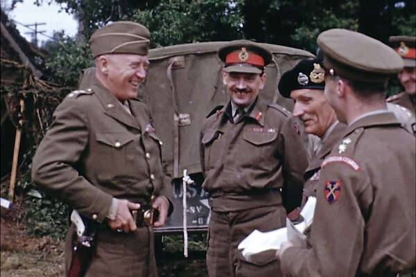 U.S. Army Gen. George Patton, left, with a pearl-handled pistol, talks to British Field Marshal Bernard Montgomery, center right with the beret hat, and other British officers in France during World War II.