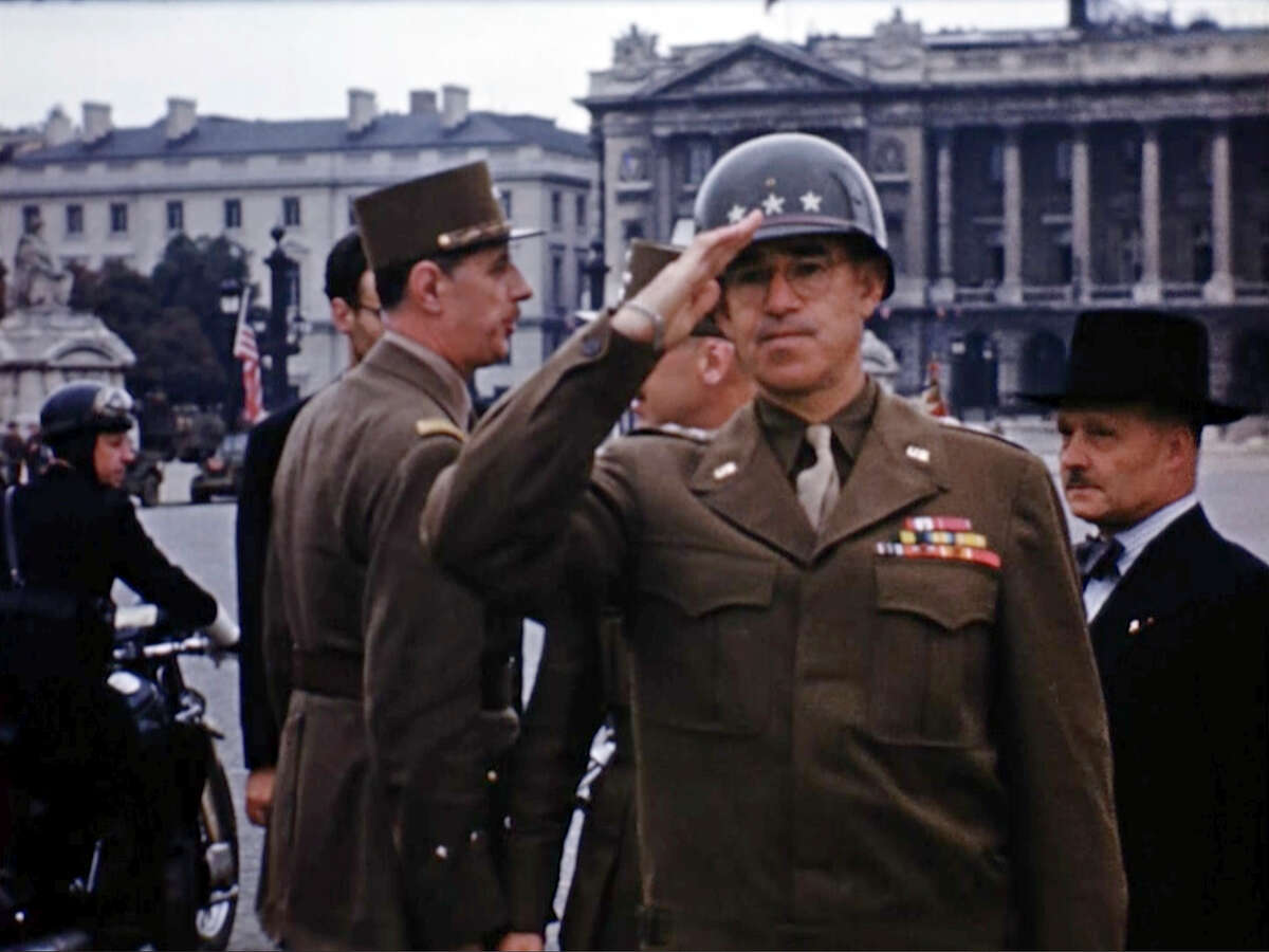 U.S. Gen. Omar Bradley salutes as Charles de Gaulle, background left, speaks before for a military parade down the Champs-Elysees after the liberation of Paris.