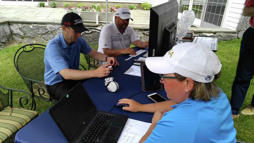 Chris Sanger of Woodstock, left, and Scott Berliner of Hiland sign their scorecards Monday, June 9, 2019, after the final round of the Donald Ross Classic at the Glens Falls Country Club. In the foreground is Tracie Warner, executive director of the Northeastern New York PGA. Berliner won the local pros' major title for the fourth straight year and seventh time overall. (Pete Dougherty / Times Union)