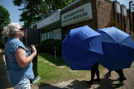 An anti-abortion protester shouts her as a woman is escorted by Clinic Escorts into the Reproductive Health Services building in Montgomery, Alabama, on May 20, 2019.