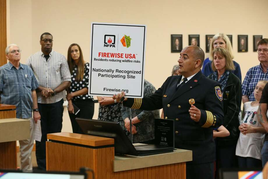 Converse Fire Chief Luis Valdez holds a sign identifying the city of Converse as a Firewise Community, as he stands in front of residents from Miramar, Northampton, Cimarron Landing and Copperfield subdivisions, during the Converse City Council meeting on June 4. Neighborhood cleanup activities in those subdivisions in May enabled the City of Converse to be the first city in Bexar County to earn the Firewise Community designation awarded by the National Fire Protection Association and the Texas A&M Forest Service. Photo: Marvin Pfeiffer /Staff Photographer / Express-News 2019