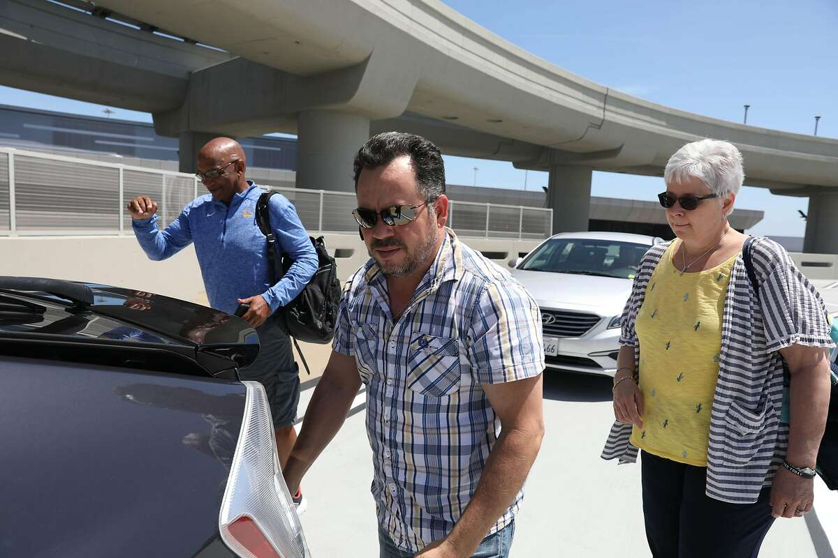 Driver Divino Couto (center) meets his passengers, Reggie Livingston and Lori Guth of Illinois, on top of the SFO parking garage in June.