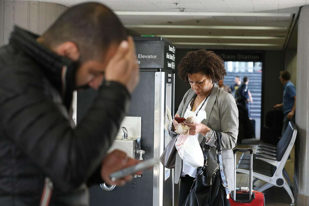 Sondra Ford (right) of New Jersey, looks for the ride app pickup area, as she stands outside the parking garage elevators on Wednesday, June 5, 2019 at San Francisco International Airport in San Francisco, Calif.