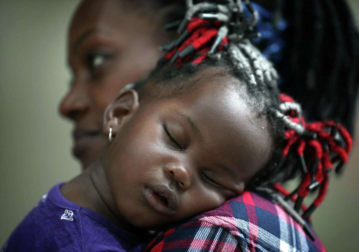 Valeria Atunga Keke, of Congo, holds her sleeping daughter Dandara Keke Makambo outside the shelter in San Antonio where she, her husband and three children have stayed for the past four days.
