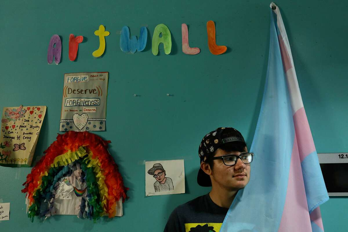 Kameron Davis, 22, stands with a Transgender Pride Flag hanging in the hallway at Thrive Youth Center, a shelter for homeless LGBTQ youth, where he lives at Haven for Hope in San Antonio on Friday, May 31, 2019.