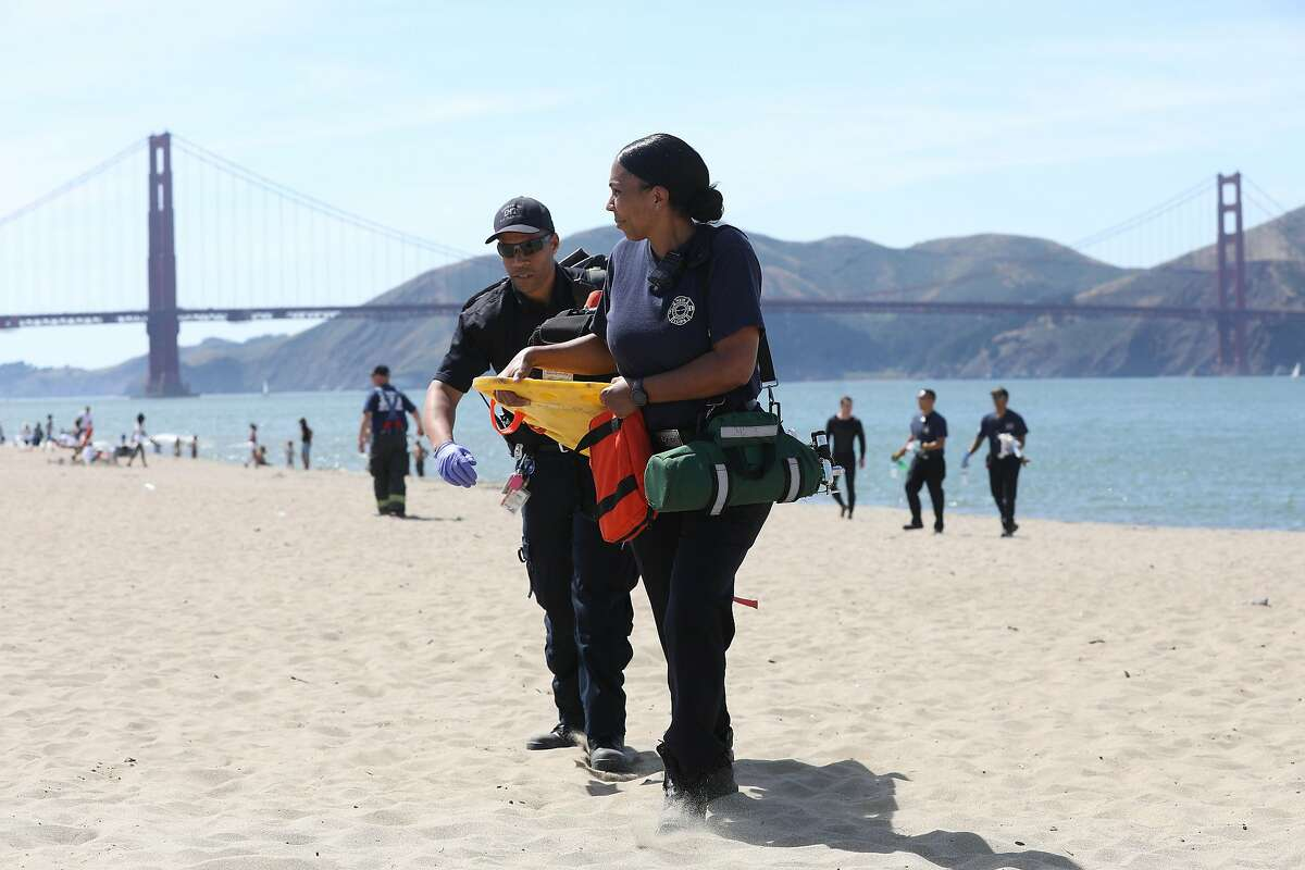 Emergency responders carry equipment on the beach at Crissy Field after a 14-year-old boy who was reported struggling in the water, was spotted after an hour and twenty minutes and rescue crews pulled him out and attempted CPR on Monday, June 10, 2019 in San Francisco, Calif.