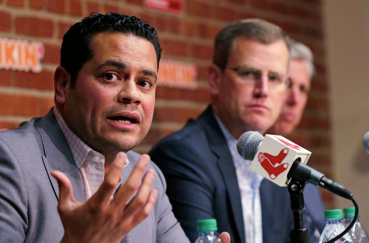 Boston Red Sox assistant general manager Eddie Romero, left, addresses the media during a news conference updating the status of former Boston Red Sox designated hitter David Ortiz at Fenway Park in Boston, Monday, June 10, 2019. Ortiz was shot at a bar Sunday night in his native Dominican Republic. Team president Sam Kennedy looks on. (AP Photo/Charles Krupa)
