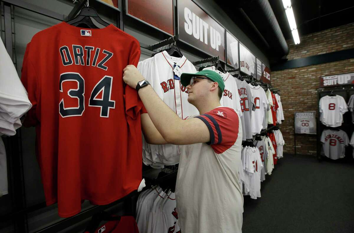 Anthony Cornwall, of Simi Valley, Calif., a fan of former Boston Red Sox slugger David Ortiz, examines a jersey featuring Ortiz' name and number at a baseball memorabilia shop near Fenway Park, in Boston, Monday, June 10, 2019. Ortiz was ambushed by a man who got off a motorcycle and shot him in the back at close range Sunday night in his native Dominican Republic, authorities said. (AP Photo/Steven Senne)