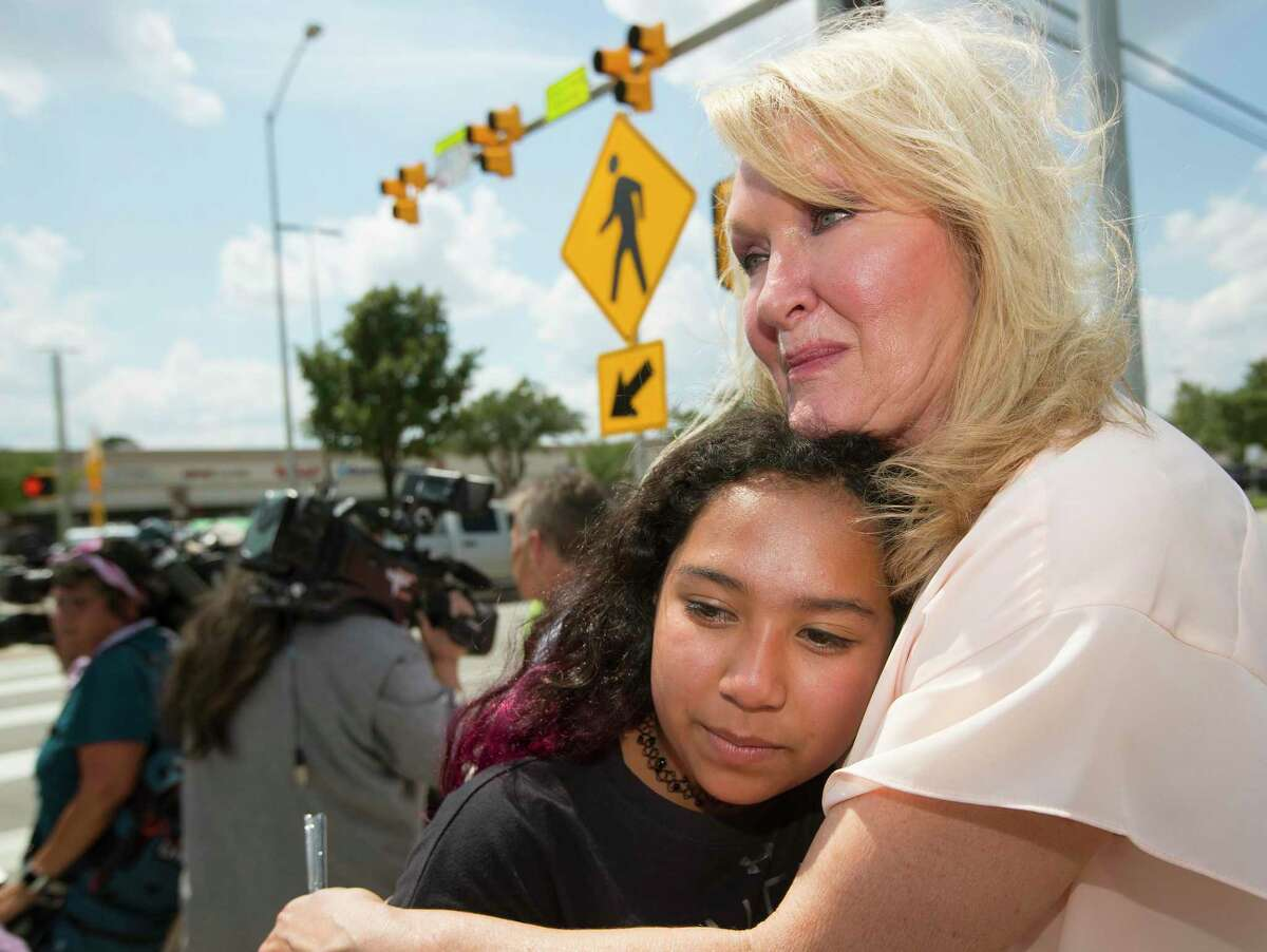 Teri Webb embraces her neice Ava Adams-Marsh near a newly-installed crosswalk light that was put in as part of the city's Safer Streets initiative on Monday, June 10, 2019, in Houston. The traffic signal was installed at the location where Lesha Adams was helping Jesus Perez, who was in a wheelchair, cross the street on March 30 and were hit and killed by a car at the intersection