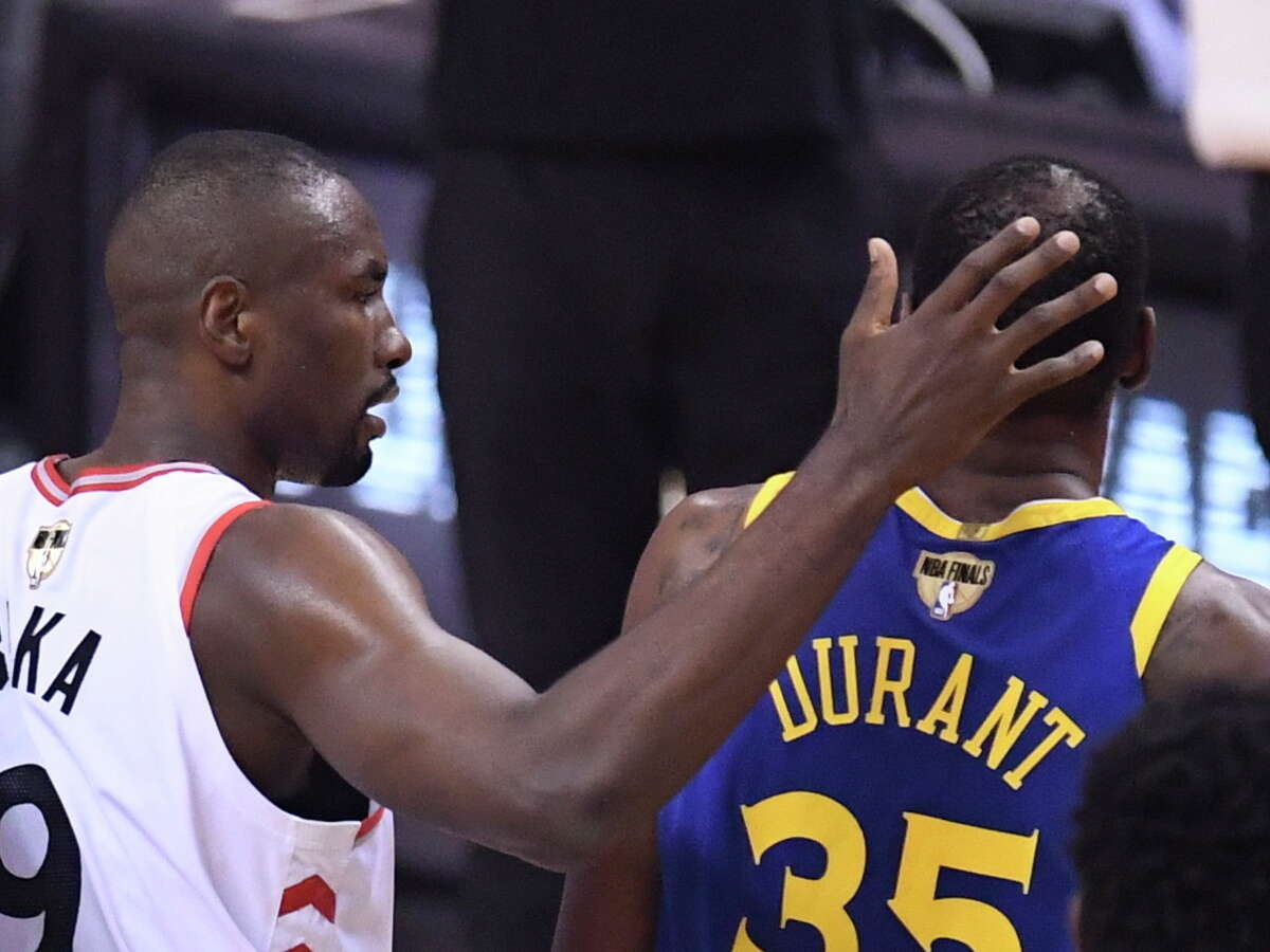 Toronto Raptors center Serge Ibaka (9) consoles Golden State Warriors forward Kevin Durant (35) as Durant leaves the first half of Game 5 of the NBA Finals in Toronto, Monday, June 10, 2019. (Frank Gunn/The Canadian Press via AP)