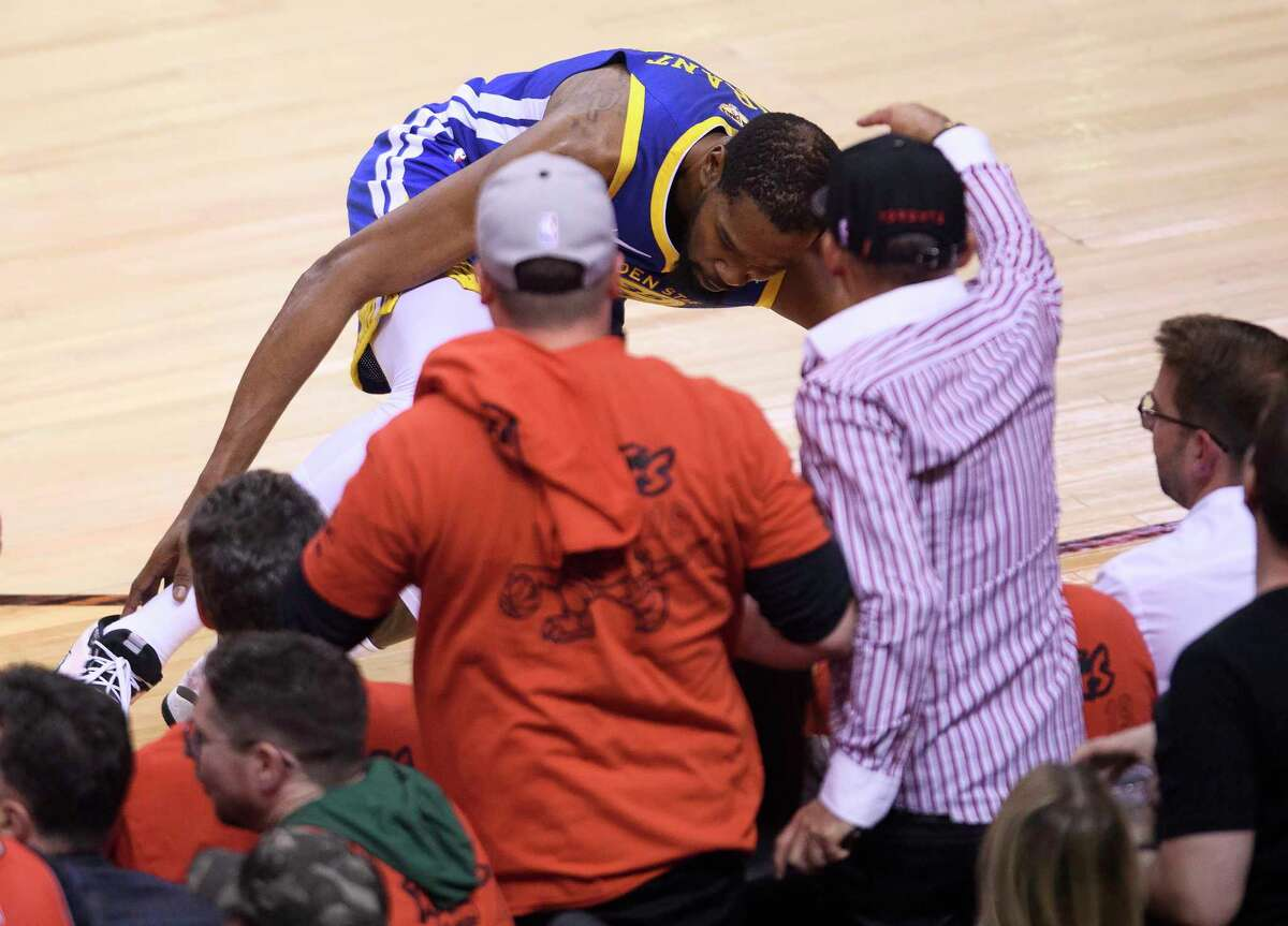 Golden State Warriors forward Kevin Durant, top, goes down grabbing the back of his leg while playing against the Toronto Raptors during first-half basketball action in Game 5 of the NBA Finals in Toronto, Monday, June 10, 2019. (Nathan Denette/The Canadian Press via AP)