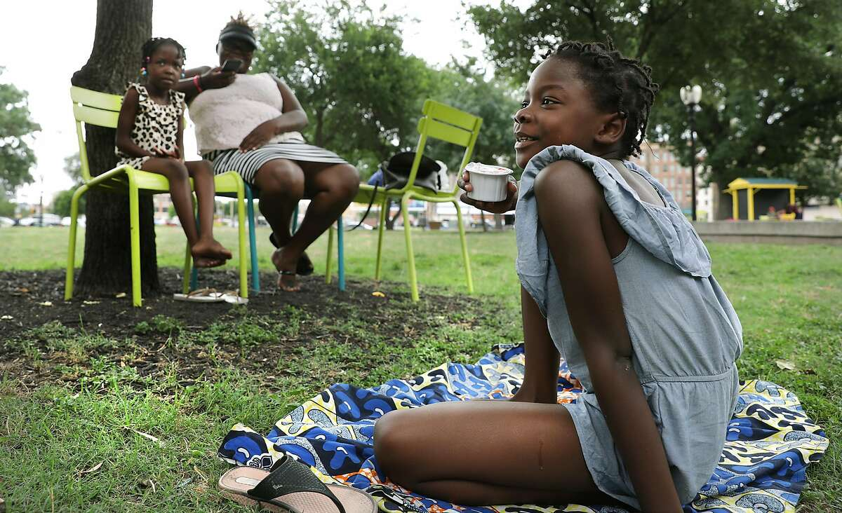 Adelaude Kiakaki, right, 8 years-old of Congo, sits in Travis Park with her sister Joyce Kiakaki, left, 6 year-old and mother Marta Cangola Mikaba, as they spend time waiting for the next leg of their jorney in the U.S.