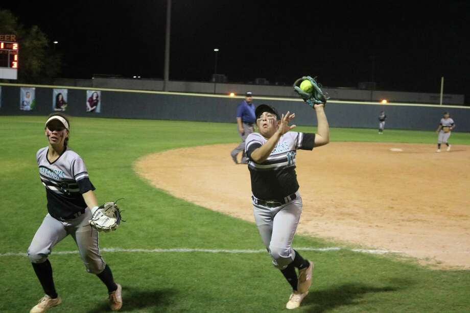 Memorial third baseman Victoria Garivey makes a nice catch of this fly ball in foul territory to end the damaging third inning Friday night. Running with her is shortstop Savana Mata. Photo: Robert Avery, HCN Staff / Robert Avery / Houston Community Newspapers
